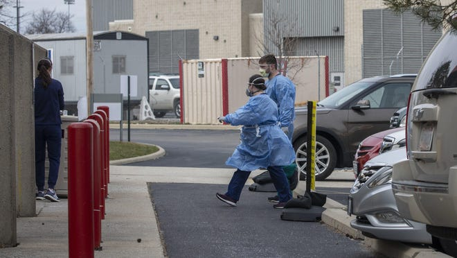 In this March 16, 2020 file photo, employees from the Ohio State Martha Morehouse Outpatient Care Center perform coronavirus testing on a patient in their car.