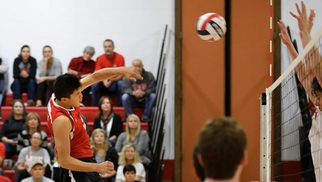 Aaron Plaisted of Wauwatosa East spikes the ball against Brookfield East.