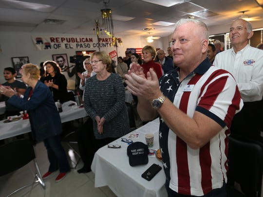 Supporters applaud newly sworn-in President Donald Trump at an open house and inauguration watch party at the GOP El Paso headquarters Friday.