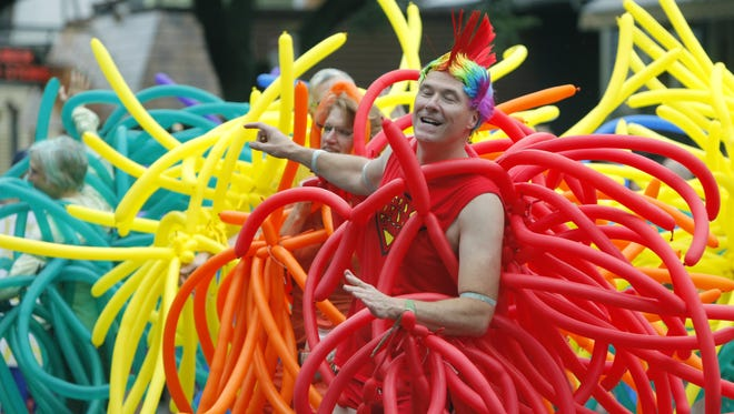 Ron Herman dances with a balloon outfit in his Park Avenue neighborhood during the Rochester Pride Parade and Festival Saturday, July 19, 2014.