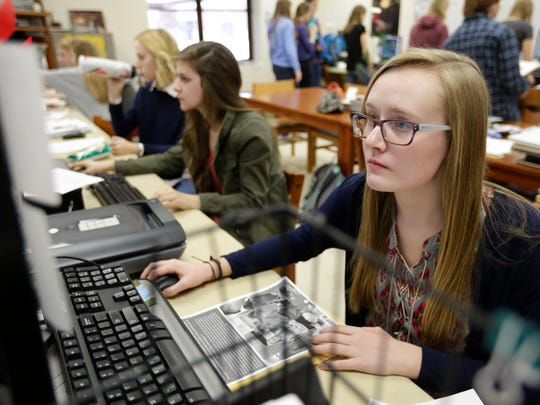 Lizzy Paul with other students work on Wahiscan, the school's yearbook, Thursday at Wausau East High School.