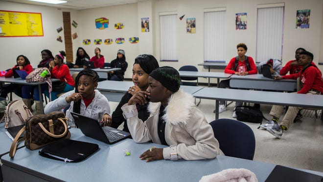 Ninth-grade students Taliyah McClinton, left, Victoria Woodley, and D'Lysa Granderson work to provide the correct answer to a U.S. History question during a quiz led by Dr. Kirkland Hamilton at Southwest Early College High on March 9, 2018.