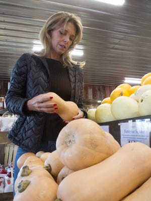 Kathy Carmichael considers a butternut squash at Simply Fresh Market in Genoa Township Monday, Nov. 20, 2017 for her vegan Thanksgiving meal.