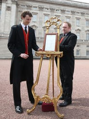 An easel is placed in the forecourt of Buckingham Palace