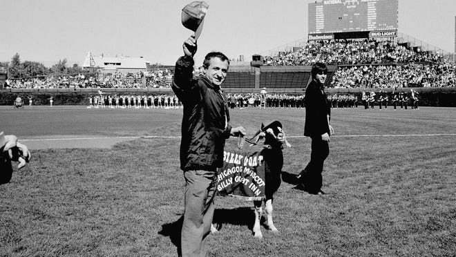 In this Oct. 2, 1984, file photo, Sam Sianis, center, owner of the Billy Goat Tavern in Chicago, acknowledges the crowd along with his goat before a National League playoff baseball game between the San Diego Padres and the Chicago Cubs.