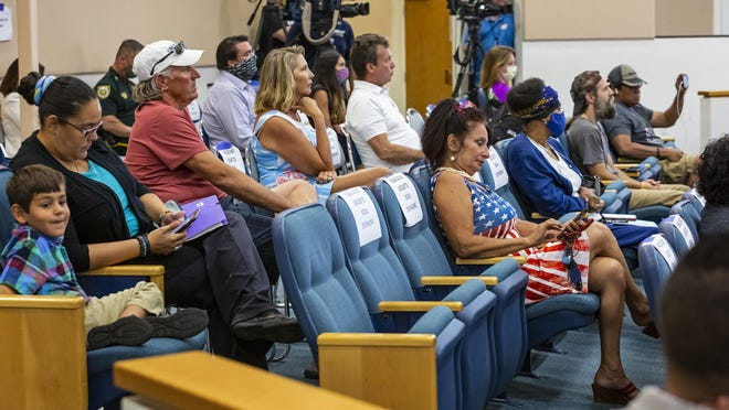 WEST PALM BEACH -- Opponents of Palm Beach County commissioners' actions on the coronavirus pandemic sit unmasked during Tuesday's commission meeting. Commissioners were scheduled on Friday to discuss opening county beaches.