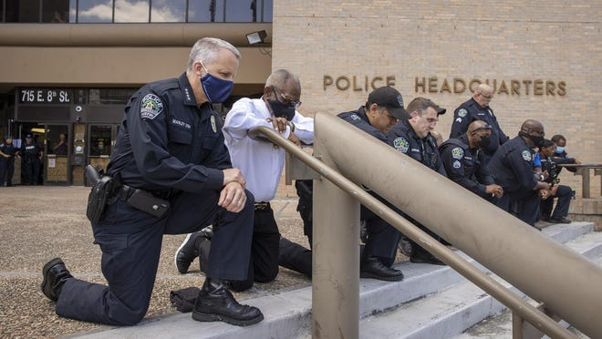 Austin Police Chief Brian Manley, left, and others kneel in memory of George Floyd at police headquarters Saturday. Several officers and protesters knelt while other protesters called the event a hollow gesture and a photo op.
