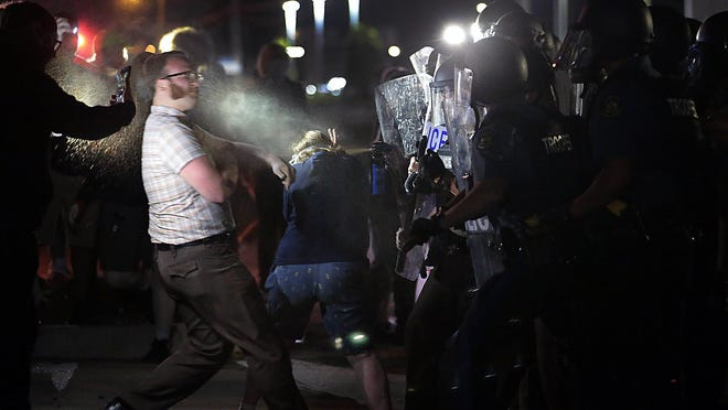 Protesters are hit with chemical spray Sunday from police officers after they arrested a man in the street while they were guarding the Florissant Police Department during a demonstration.