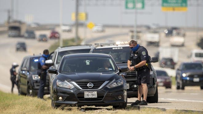 Austin police officers pull over drivers on East Ben White Boulevard on Aug. 31. A report released Monday found that Black motorists in Austin were overrepresented in traffic stops in 2019.