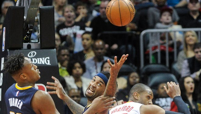 Indiana Pacers center Jordan Hill reaches for a rebound above the back of Atlanta Hawks center Al Horford 15) as Pacers forward Myles Turner (33) watches during the first half of an NBA basketball game, Friday Feb. 5, 2016, in Atlanta. (AP Photo/John Amis)