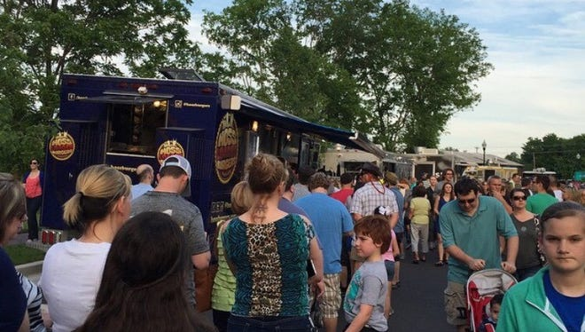 Customers line up outside Dallas Shaw's Hoss' Loaded Burgers food truck alongside other mobile food vendors.