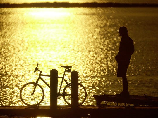 A University of Vermont junior from Southampton NY majoring in English and Philosophy, takes a break from his studies to ride his bike down to Burlington's Waterfront Park and enjoy the sunset in 2002 (from the photo archive)