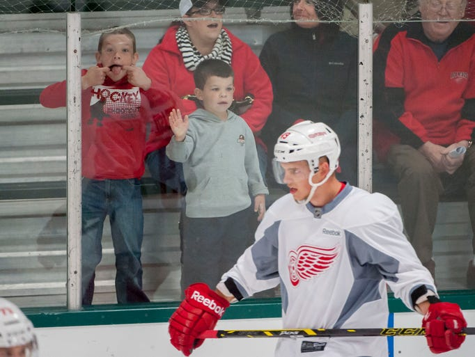 Young fans try to get the attention of Brennan Evans and the rest of the players during the first day of the Detroit Red Wings training camp at Centre Ice Arena in Traverse City, September 19, 2014.