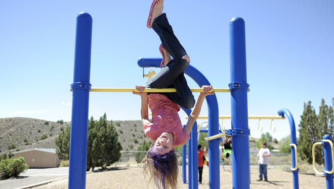 Daylynn Heitzenrater plays on the monkey bars on May 28, 2014, at Naaba Ani Elementary in Bloomfield.