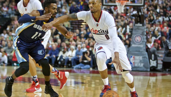 Portland Trail Blazers guard Damian Lillard, right, dribbles past Memphis Grizzlies guard Mike Conley during the first half of an NBA basketball game in Portland, Thursday, Nov. 5, 2015.