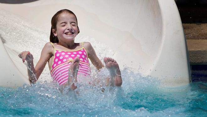 Jadin Stewart, 11, slides into the pool  at Eldorado Aquatic and Fitness Center in Scottsdale.