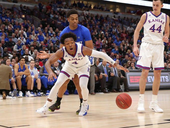 Kansas Jayhawks guard Devonte' Graham (4) reaches for