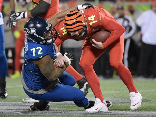 NFC defensive end Michael Bennett (72), of the Seattle Seahawks, sacks AFC quarterback Andy Dalton (14), of the Cincinnati Bengals, during the first half of the NFL Pro Bowl football game Sunday, Jan. 29, 2017, in Orlando, Fla.