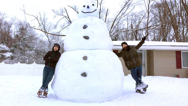 Thomas Wallace (right) of Vineland, and his friend made this 10 foot snowman located at 1239 Oak Lane.