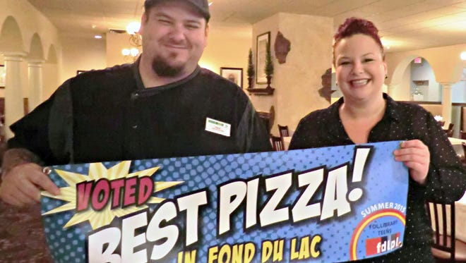 Executive Chef Tim Burk and restaurant General Manager Betsy Calabresa show off the banner Benvenuto's Italian Grill received for winning the blind taste-test at the Fond du Lac Public Library's Mega-Pizza Party for teens. The party wrapped up the 11-week summer reading program, and the teens crowned their favorite pie while scoring prizes and enjoying activities.