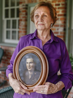 Mildred Sturlese, widow of World War II Army Air Forces pilot Adam Moise Sturlese, wholds a photo of him at her home in Lafayette Nov. 11, 2016.