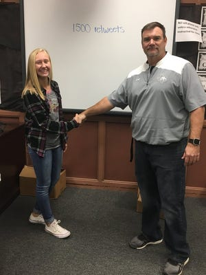 Water Valley athlete Brittany Sutton and head football coach Keith Woolf shake on their Twitter bet in 2017. Woolf agreed to don 1980s-era workout gear and join the Lady Wildcats in a workout if Sutton could get 1,500 people to retweet. It took less than two days to reach the number.