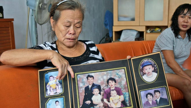 Suwarni, the mother of Sugianto Lo, who was onboard the missing Malaysia Airlines Flight 370 with his wife Vinny, shows her son's family portraits at her residence in Medan, North Sumatra, Indonesia on March 25, 2014.