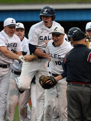 Lancaster's Garrett Strang, center, celebrates his home run with his teammates during Thursday night's game at Beavers Field in Lancaster. The Golden Gales' game with Fairfield Union was suspended due to rain with Lancaster winning 4-0 in the bottom of the fourth inning.