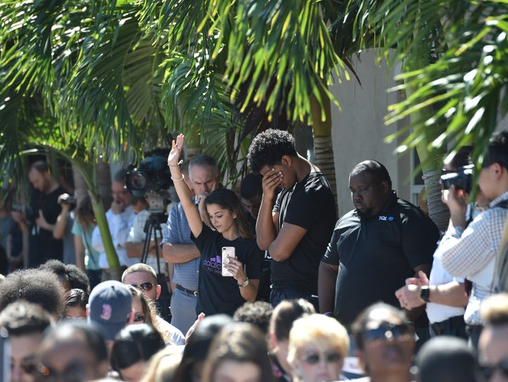Students bow their heads in prayer along with the crowd