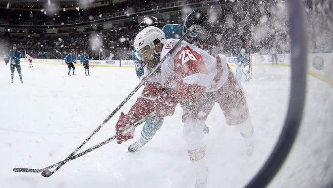 Luke Witkowski of the Red Wings and Eric Fehr of the Sharks battle for the puck in the first period at SAP Center on Monday night.
