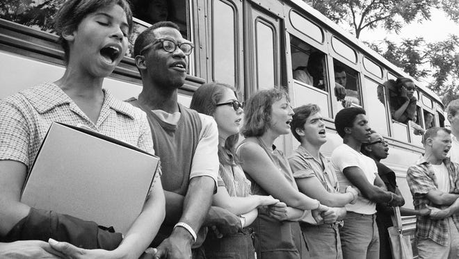 Student civil rights activists join hands and sing as they prepare to leave Ohio to register black voters in Mississippi. The 1964 voter registration campaign was known as Freedom Summer.