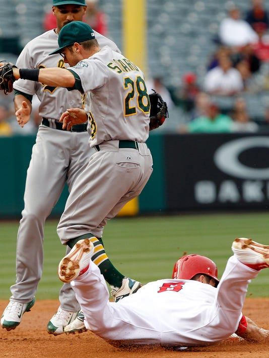 Oakland Athletics second baseman Eric Sogard (28) beats a sliding Los Angeles Angels' David Freese (6) to second base for an unassisted force out, with shortstop Marcus Semien watching, to end the third inning of a baseball game in Anaheim, Calif., Thursday, April 23, 2015. (AP Photo/Alex Gallardo)