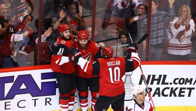 Mar 31, 2017; Glendale, AZ, USA; Arizona Coyotes center Alexander Burmistrov (91) celebrates a goal with Max Domi (16) and Anthony Duclair (10) against the Washington Capitals in the second period at Gila River Arena.