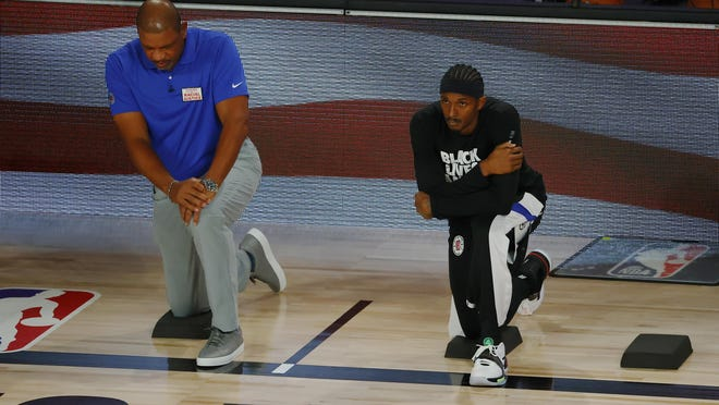 Lou Williams and head coach Doc Rivers of the LA Clippers look on during the national anthem before the start of a game against the Dallas Mavericks in Game Four of the Western Conference First Round during the 2020 NBA Playoffs at AdventHealth Arena at ESPN Wide World Of Sports Complex on Sunday, in Lake Buena Vista, Florida.