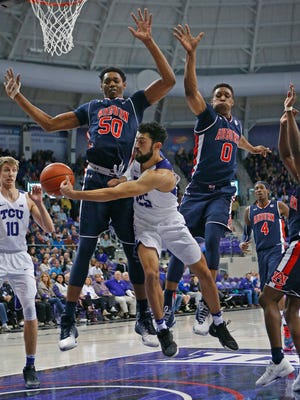 TCU guard Alex Robinson (25) passes to forward Vladimir Brodziansky (10) under the basket and past Auburn defenders Austin Wiley (50) and Horace Spancer (9) during the second half of an NCAA college basketball game in Fort Worth, Texas, Saturday, Jan. 28, 2017. (Paul Moseley/Star-Telegram via AP)