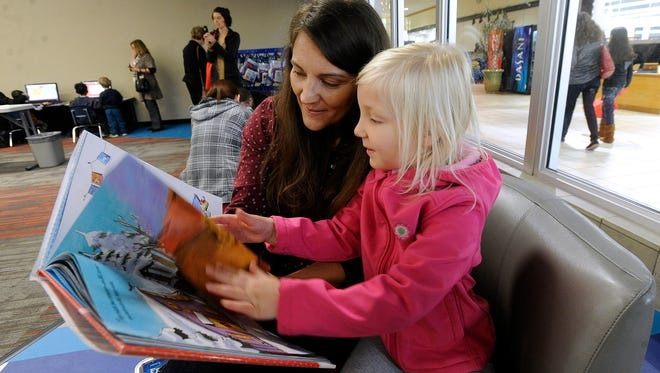 "Haley Brown, 5, reads ""How Many Sleeps Till Christmas?"" with her mother, Ami, during the opening of the Abilene Public Library's new south branch location at the Mall of Abilene on Saturday, Nov. 19, 2016."