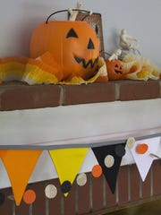 Black, white, orange and yellow pennants evoke Halloween and candy corn in a banner hanging from a fireplace mantel. The pennants can be removed and replaced with other colors for the next holiday.