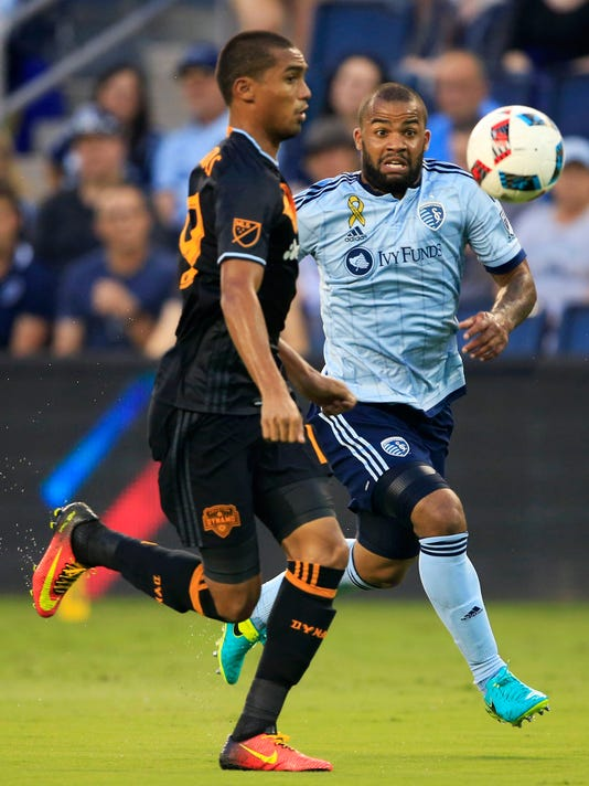 Houston Dynamo forward Mauro Manotas (19) and Sporting Kansas City defender Kevin Ellis, right, race for the ball during the first half of an MLS soccer match in Kansas City, Kan., Friday, Sept. 9, 2016. (AP Photo/Orlin Wagner)