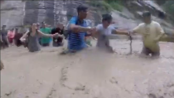 This July 29, 2017, image shows hikers forming a human chain to cross a river swollen with flash flood waters in the red-rock Utah Desert at Zion National Park in Utah. Jhonatan Gonzalez and his brothers originally stood in the water together to help several younger family members cross the river, then others joined in.