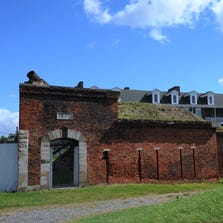 Exterior view of the main entrance to Fort Wayne and the historic barracks behind the gate.