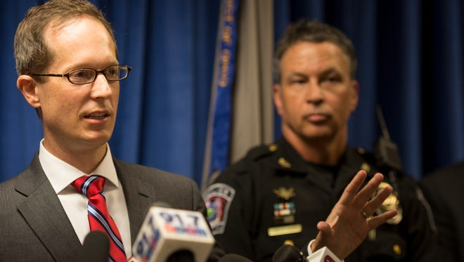 Benjamin C. Glassman, acting U.S. Attorney for the Southern District of Ohio, stands with Newtown Police Chief Tom Synan of the Heroin Task Force during a press conference announcing a federal indictment of two Cincinnati residents, alleging that they distributed heroin laced with carfentanil.