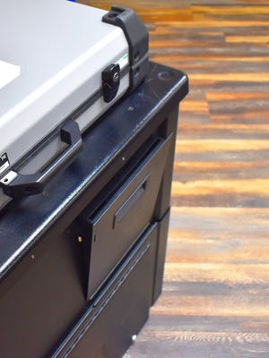 A small slot hangs open on the front of a voting machine on Tuesday. The electronic machine has a low-tech lock box available so ballots can be safely recorded in the event of a power outage.