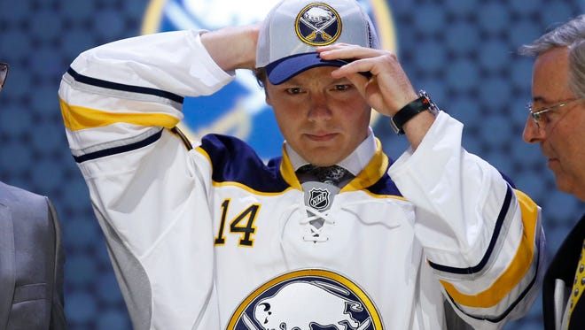 Sam Reinhart pulls on a Buffalo Sabres hat after being chosen second overall during the first round of the NHL hockey draft on Friday in Philadelphia.