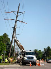 Workers from Xcel Energy replace broken power poles along Second Street South Monday, June 12, in Waite Park. The wind damage from Sunday mornings storm toppled trees and broke power poles.