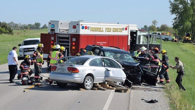 Emergency responders including firefighters with the Grinnell Fire Department, Midwest Ambulance and the Iowa State Patrol work to extricate victims from a two-car head-on collision that killed three people on U.S. Highway 146 south of Grinnell.