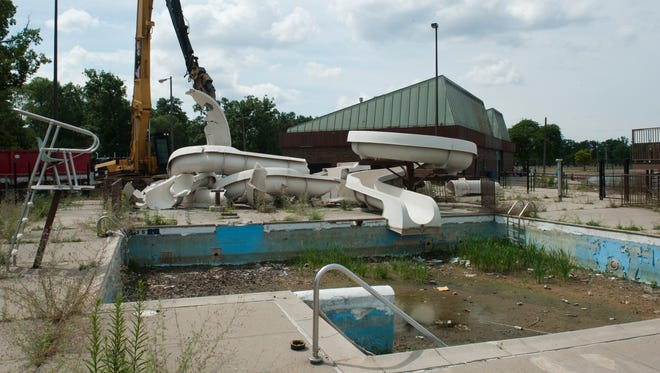 A heavy-machine claw lifts a broken section of waterslide to a dumpster truck as a demolition crew dismantles the old waterslide on Detroit's Belle Isle on Monday, July 30, 2018. The dormant slide opened in 1996 and has been closed for years.