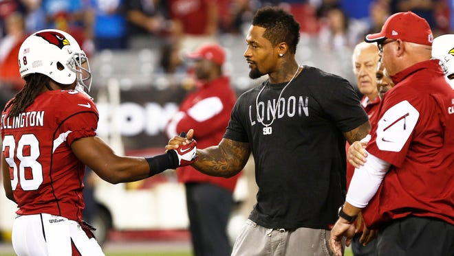 Andre Ellington greets Darnell Dockett before playing the San Diego Chargers during Monday Night Football on Sep. 8, 2014 at University of Phoenix Stadium in Glendale.