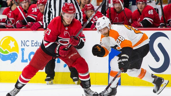 Philadelphia Flyers' Claude Giroux (28) reaches for the puck ahead of Carolina Hurricanes' Brock McGinn (23) during the second period of an NHL hockey game in Raleigh, N.C., Saturday, March 17, 2018. (AP Photo/Ben McKeown)