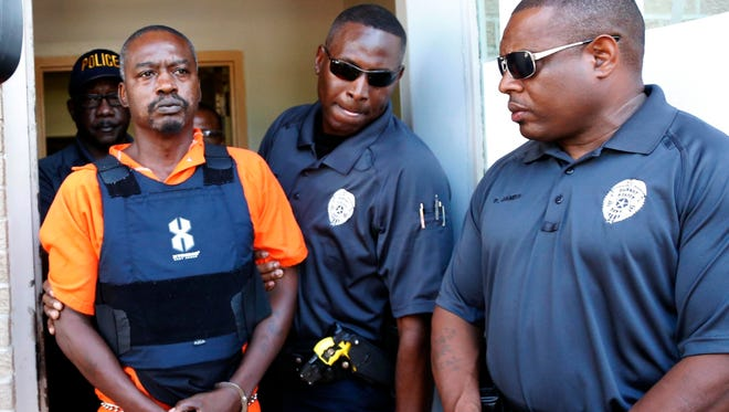 Durant police surround Rodney Earl Sanders, of Kosciusko as he leaves the Durant Municipal Building after an initial appearance in municipal court Monday in Durant. Sanders was charged with two counts of capital murder in the slayings of nuns Margaret Held and Paula Merrill, both 68.
