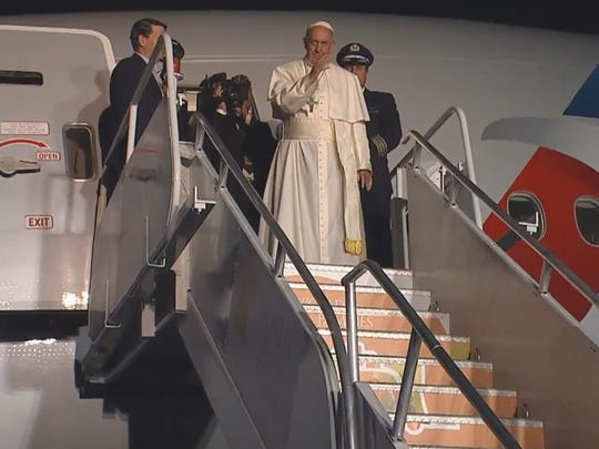 Pope Francis gives a wave to officials before boarding his plane back to Rome.